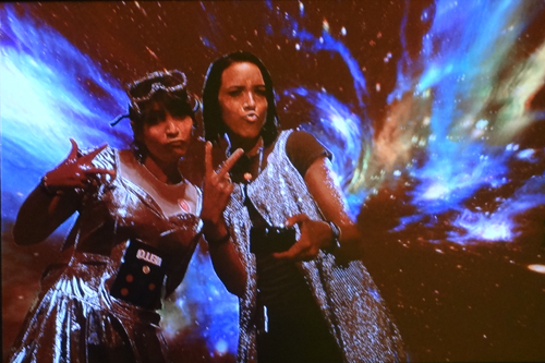 Amber and a friend in cheap silver costumes, making silly duck faces and throwing peace signs in front of a picture of space. A filter makes their colouring look alien.