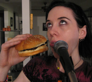 Me with my mouth between a burger and a mic, sticking my tongue out like it's such a burden to want those things
