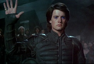 Screenshot from David Lynch's Dune: Paul Atreides in a Fremen stillsuit and blue-in-blue eyes