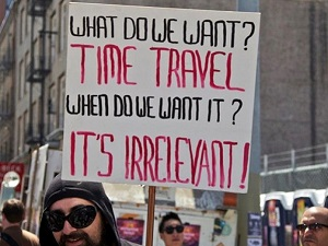Man holds a sign with the text: What do we want? Time Travel! When do we want it? It's Irrelevant!