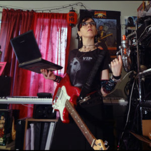 Me posing with a guitar, a laptop, and a plastic laser pistol in front of music gear and a poster of Buckaroo Banzai