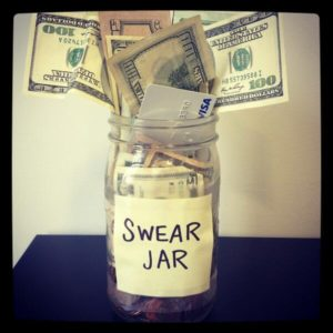 "A jar labelled ""swear jar"" and filled with large denominations of money and a credit card"