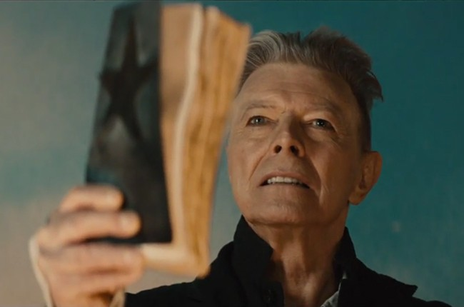 David Bowie in the Blackstar video, holding up a battered book with a black star on the cover